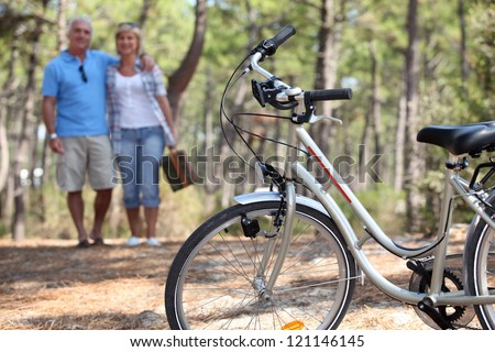 Middle-aged couple cycling - stock photo
