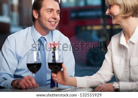 Middle aged couple drinking red wine at an outdoor cafe.