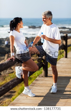 middle aged couple drinking water after exercising on beach - stock photo