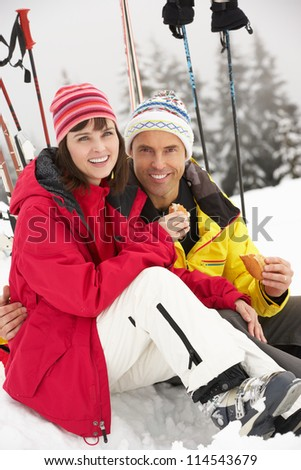Middle Aged Couple Eating Sandwich On Ski Holiday In Mountains - stock photo