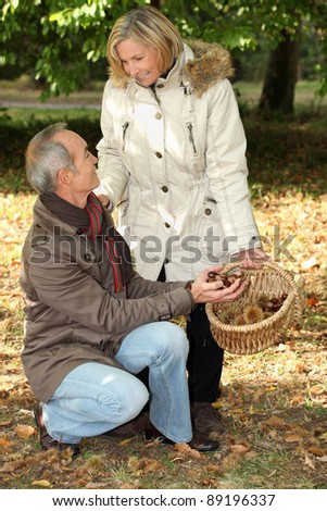 Middle aged couple going chestnut picking. - stock photo