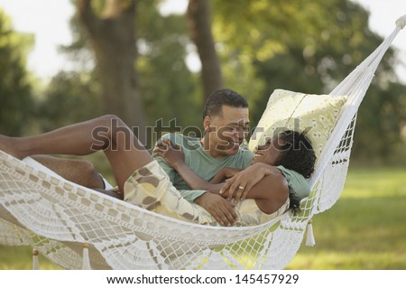 Middle-aged couple hugging in hammock - stock photo