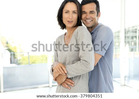 Middle-aged couple hugging in new apartment - stock photo