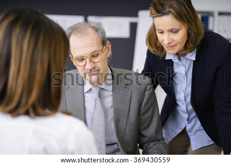 Middle-aged couple in a business meeting with a female colleague or broker busy reading paperwork with serious expressions