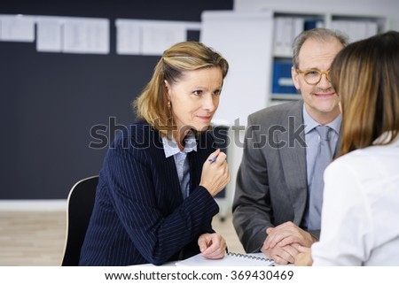 Middle-aged couple in a meeting with a female agent or broker listening attentively to her with a smile, over the shoulder view - stock photo