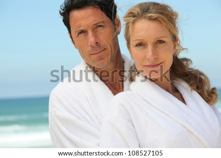 Middle-aged couple in bathrobe - stock photo