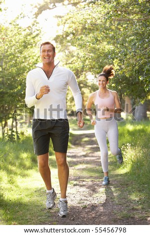 Middle Aged Couple Jogging In Park - stock photo