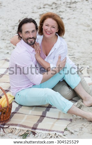 Middle-aged couple kissing and enjoying their evening. Beautiful people resting at the beach during the sunset. - stock photo