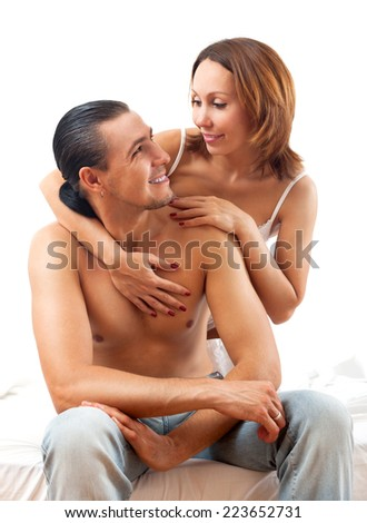 Middle-aged couple kissing and playing on white sheet in bed at home  - stock photo