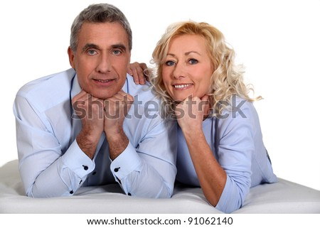 Middle-aged couple laying together - stock photo