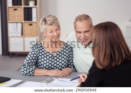Middle Aged Couple Listening to a Female Agent Discussing Some Business to them at the Table. - stock photo