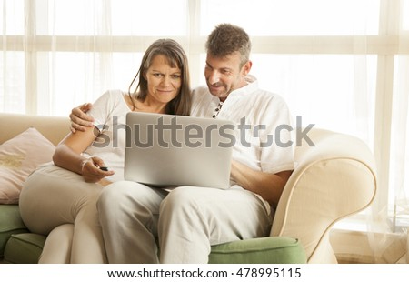 middle aged couple looking at a computer and smile