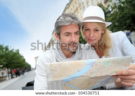 Middle aged couple looking at city map - stock photo