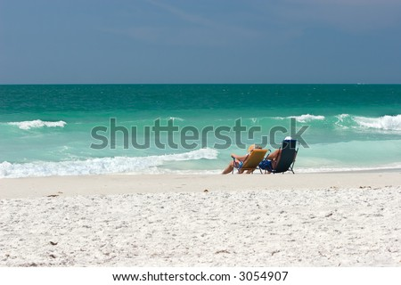 Middle-aged couple lounging at the water's edge on the Treasure Island, Florida public beach.