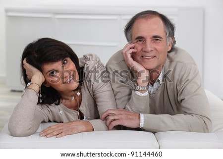 Middle-aged couple lying on a futon - stock photo