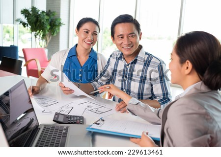 Middle-aged couple meeting financial adviser for real estate project - stock photo