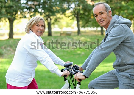 Middle-aged couple on bike ride - stock photo