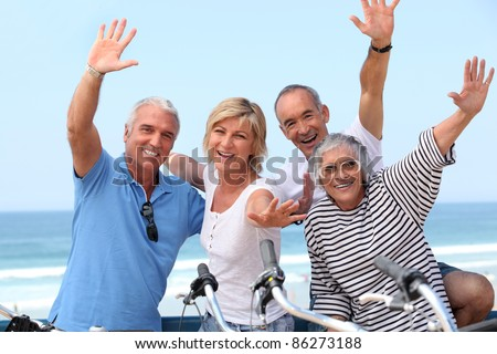 Middle-aged couple on bike ride by the sea - stock photo