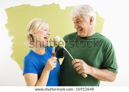 Middle-aged couple painting wall green playing with paint utensils. - stock photo