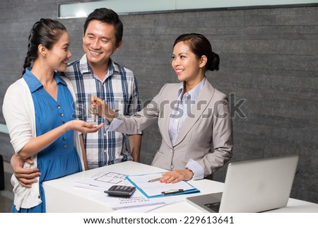Middle-aged couple receiving the keys from the new apartment - stock photo