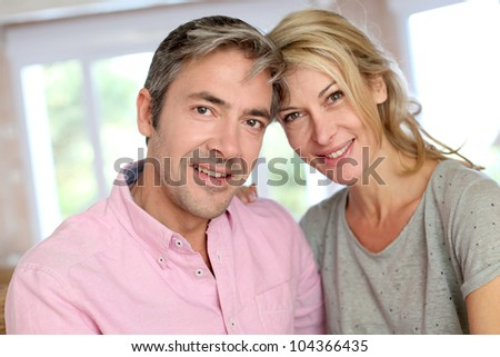 Middle aged couple relaxing in sofa at home - stock photo