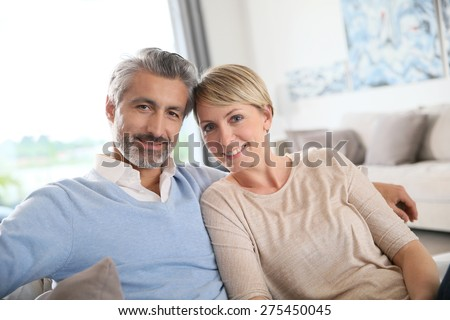 Middle-aged couple relaxing in sofa at home - stock photo