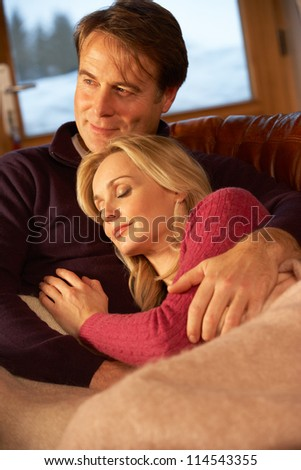 Middle Aged Couple Relaxing On Sofa In Chalet With Winter View - stock photo