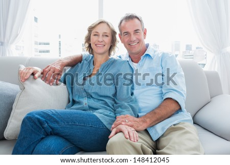 Middle aged couple relaxing on the couch smiling at camera at home in the living room - stock photo