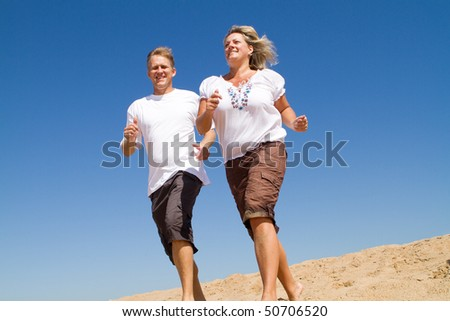 middle-aged couple running on beach, background is blue sky