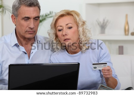 Middle aged couple shopping online. - stock photo