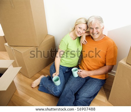 Middle-aged couple sitting on floor among cardboard moving boxes with coffee. - stock photo