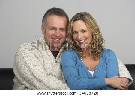 Middle Aged Couple Sitting On Sofa - stock photo