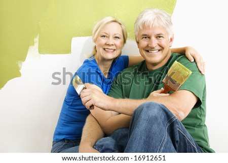 Middle-aged couple snuggling in front of wall they are painting green. - stock photo