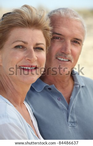 Middle-aged couple stood on beach - stock photo