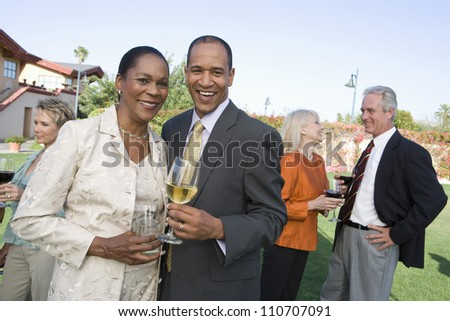 Middle aged couple toasting wine together