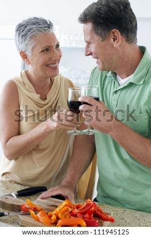 Middle aged couple toasting with red wine - stock photo