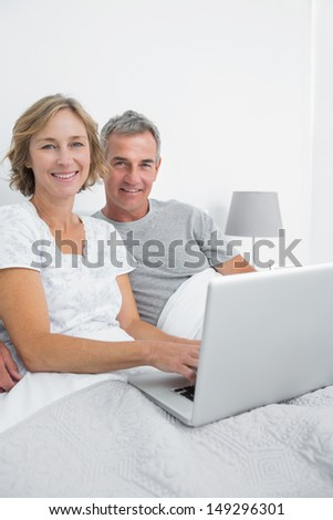 Middle aged couple using their laptop together in bed smiling at camera at home in bedroom