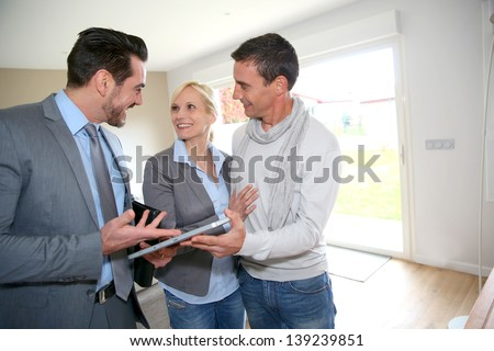 Middle-aged couple visiting house with salesman - stock photo