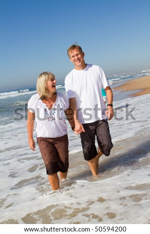 middle-aged couple walking on beach - stock photo