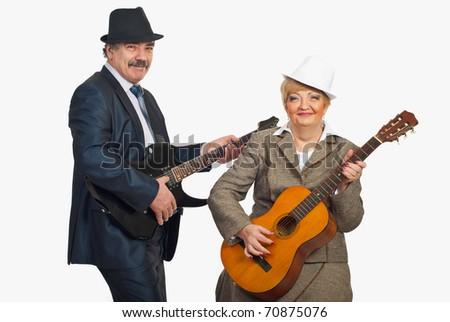 Middle aged couple wearing hats and elegant suits and playing guitars isolated on white background