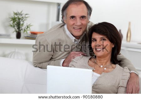 Middle-aged couple with laptop - stock photo