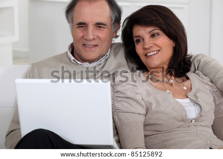 Middle-aged couple with laptop sat on sofa - stock photo
