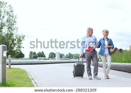 Middle-aged couple with luggage walking on footpath against clear sky - stock photo