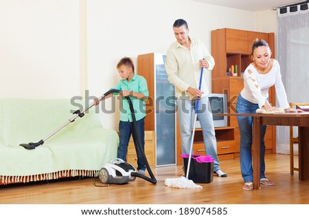 middle-aged couple with teenage son doing house cleaning  in living room at home - stock photo