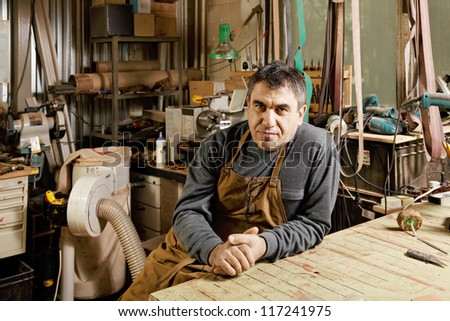 Middle-aged craftsman sitting in his workshop at workbench - stock photo