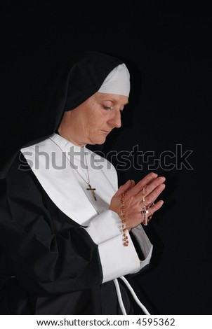 Middle aged devout nun in deep thoughts, praying.  Religion, christianity, lifestyle concept - stock photo