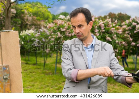 Middle-aged fashionable handsome male painter cleaning off his paintbrush with a rag and looking at his picture on a sketchbook in a park - stock photo