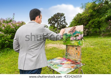 Middle-aged fashionable male painter working on a sketchbook painting a garden scene with flowers outdoors - stock photo