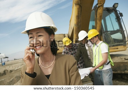Middle aged female architect using cell phone with workers working in background at construction site - stock photo