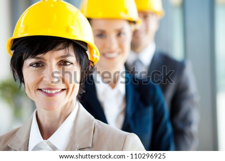 middle aged female construction business leader and team - stock photo